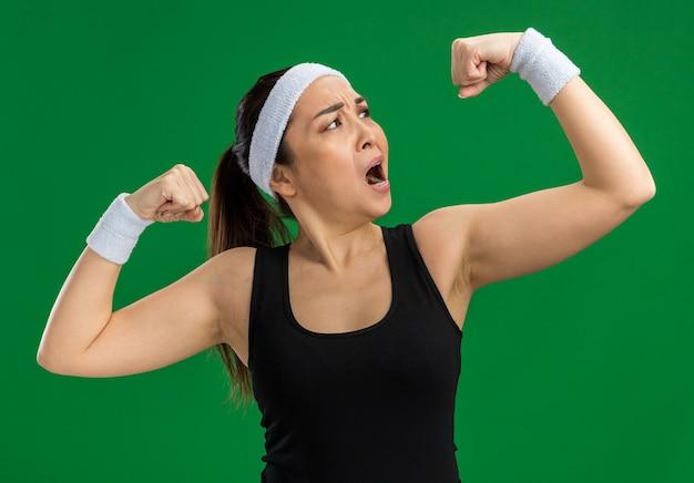 Junge fitnessfrau mit stirnband und armbinden, die angespannt aussieht und die fäuste hebt, die den bizeps zeigen, der über der grünen wand steht