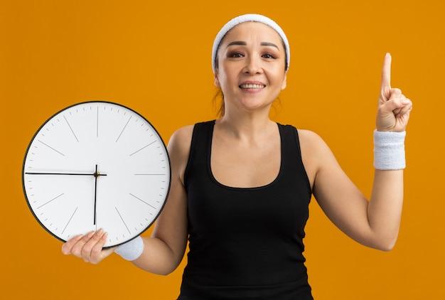 Junge fitnessfrau mit stirnband und armbinden, die eine wanduhr mit glücklichem gesicht hält, das mit dem zeigefinger nach oben zeigt