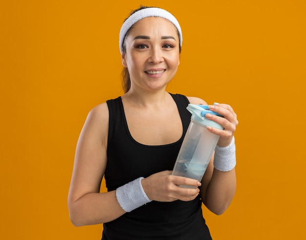 Junge fitnessfrau mit stirnband und armbinden, die eine wasserflasche mit einem lächeln auf dem gesicht hält, die über der orangefarbenen wand steht