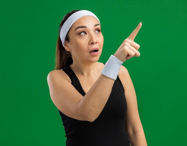 Junge fitnessfrau mit stirnband und armbinden, die fasziniert beiseite schaut und mit dem zeigefinger auf etwas zeigt, das über grüner wand steht standing