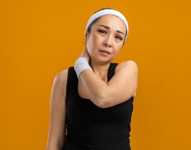 Junge fitnessfrau mit stirnband und armbinden, die ihren hals hält und unwohl sieht, schmerzen fühlen