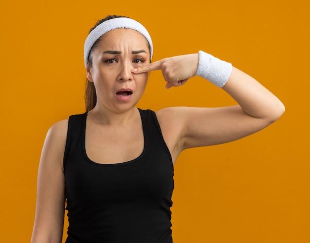 Junge fitnessfrau mit stirnband und armbinden, die mit dem zeigefinger auf ihre nase zeigt und verwirrt aussieht looking