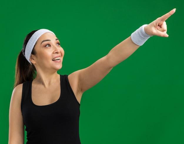 Junge fitnessfrau mit stirnband und armbinden, die mit einem lächeln auf dem gesicht zur seite schaut und mit dem zeigefinger zur seite zeigt