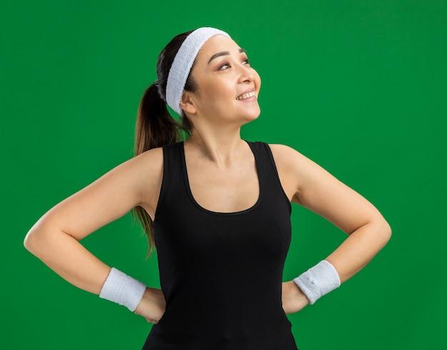 Junge fitnessfrau mit stirnband und armbinden, die mit einem lächeln im gesicht mit den armen an der hüfte beiseite schaut