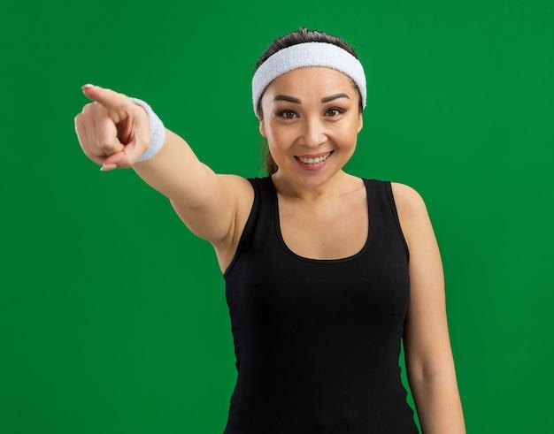 Junge fitnessfrau mit stirnband und armbinden, die selbstbewusst lächelt und mit dem zeigefinger über der grünen wand steht