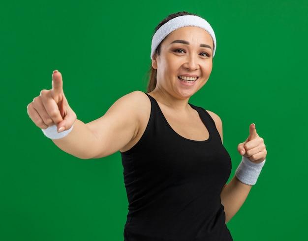 Junge fitnessfrau mit stirnband und armbinden, die selbstbewusst lächelt und mit den zeigefingern über der grünen wand steht standing