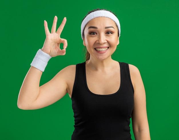 Junge fitnessfrau mit stirnband und armbinden mit einem lächeln im gesicht, das ein gutes zeichen macht