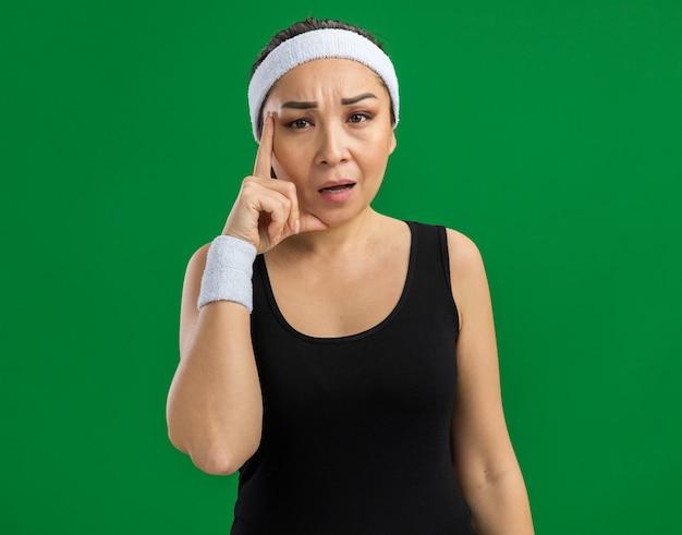 Junge fitnessfrau mit stirnband und armbinden mit ernstem gesicht, das mit dem zeigefinger auf den tempel zeigt, der über grüner wand steht