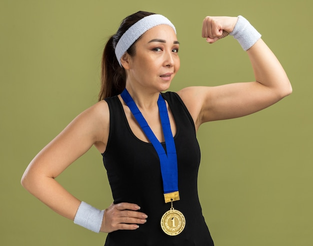 Junge fitnessfrau mit stirnband und armbinden mit goldmedaille um den hals, die selbstbewusst die faust hebt und bizeps zeigt