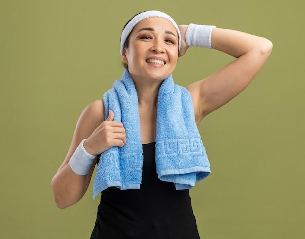 Junge fitnessfrau mit stirnband und handtuch um den hals mit einem lächeln im gesicht