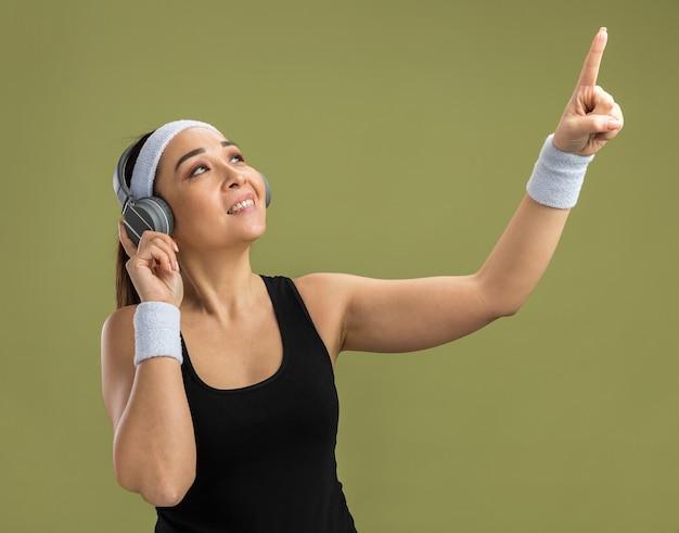 Junge fitnessfrau mit stirnband und kopfhörern, die ihre lieblingsmusik genießt und mit dem zeigefinger nach oben zeigt, lächelnd über grüner wand stehend