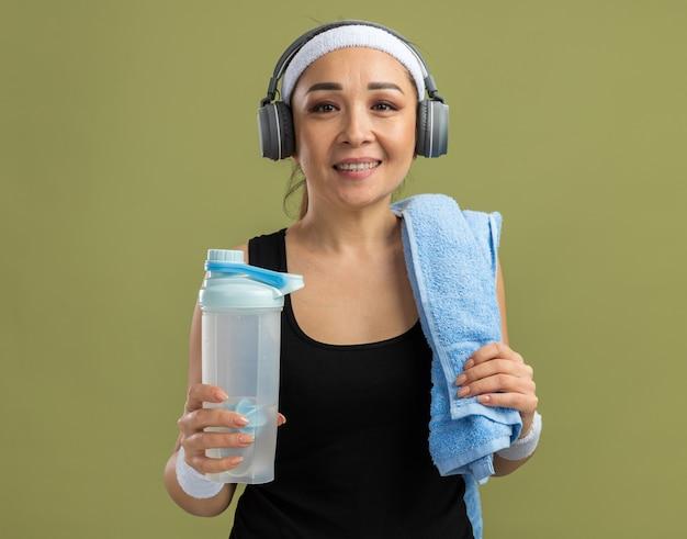 Junge fitnessfrau mit stirnband und kopfhörern mit handtuch auf der schulter, die eine wasserflasche mit einem lächeln im gesicht hält, die über grüner wand steht