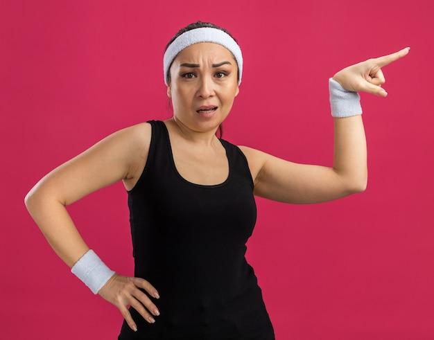 Junge fitnessfrau mit stirnband verwirrt, die mit dem zeigefinger auf die seite zeigt, die über rosa wand steht