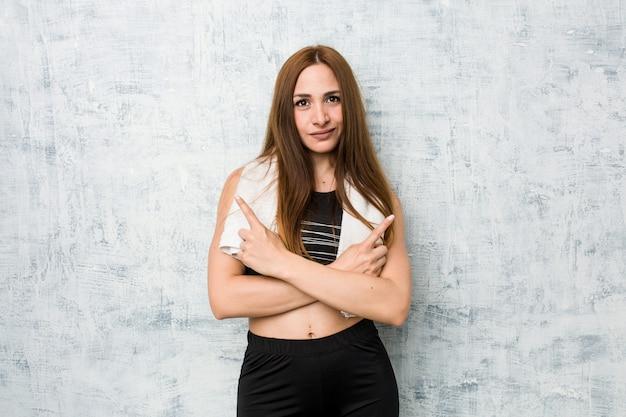 Junge fitnessfrau zeigt seitwärts, versucht zwischen zwei optionen zu wählen.