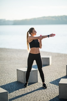 Junge fitnessfrauenläuferin, die vor dem lauf beine ausdehnt