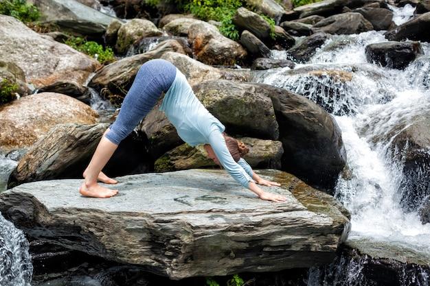 Junge fitte frau, die yoga draußen am wasserfall tut