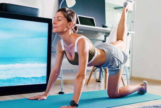Junge fitte frau, die yoga-hunde- oder katzenpose-dehnungsübung innen nahe fernsehbildschirm auf isolation an ihrem haus tut Premium Fotos