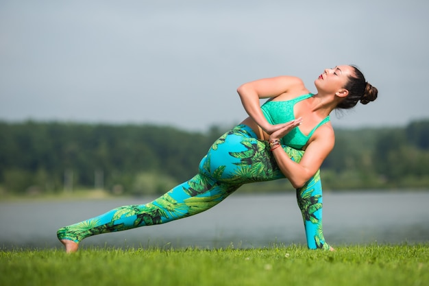 Junge fitte frau, die yoga im freien im park praktiziert