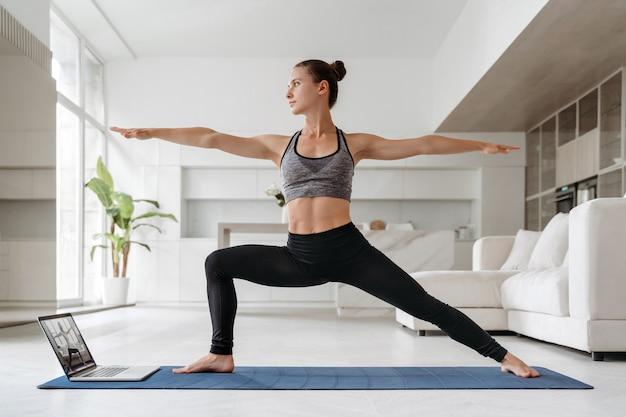 Junge fitte frau, die zu hause yoga mit laptop praktiziert