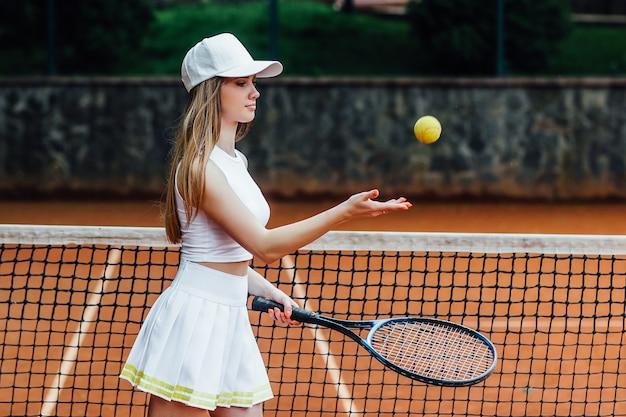 Junge fitte frau in mütze und tennisuniform mit tennisball während des trainings auf dem tennisplatz im freien.