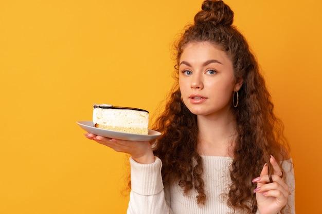Junge fitte lockige frau mit einem stück kuchen vor gelbem hintergrund