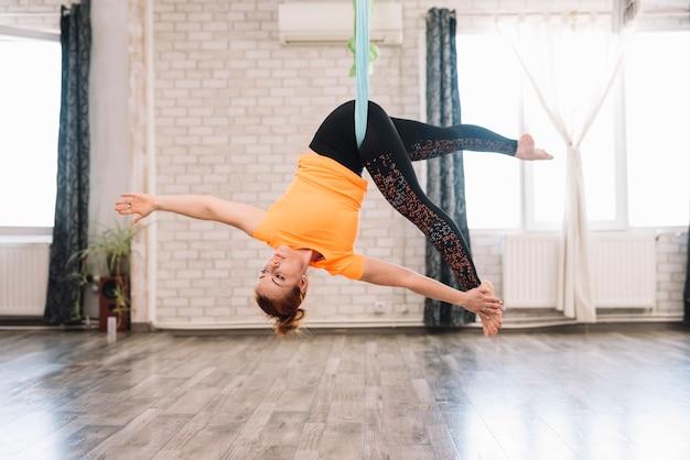 Junge flexible gesunde frau, die luftyoga in der turnhalle tut