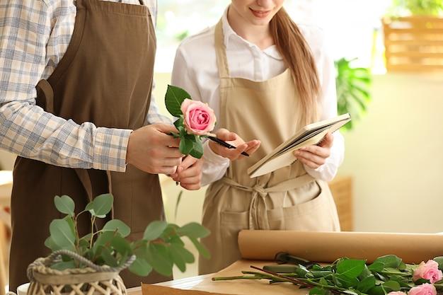 Junge floristen, die im geschäft arbeiten