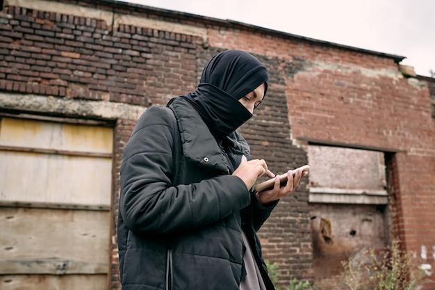 Junge flüchtlingsfrau im hijab-sms im handy