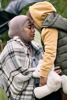 Junge flüchtlingsfrau und ihre kleine tochter mit spielzeug