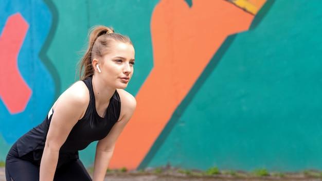 Junge fokussierte blonde frau beim training im freien, das nach dem laufen mehrfarbigen hintergrund ruht