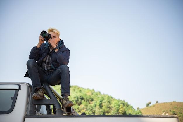 Junge fotograf sitzt auf seinem pickup lkw fotografiert in berg