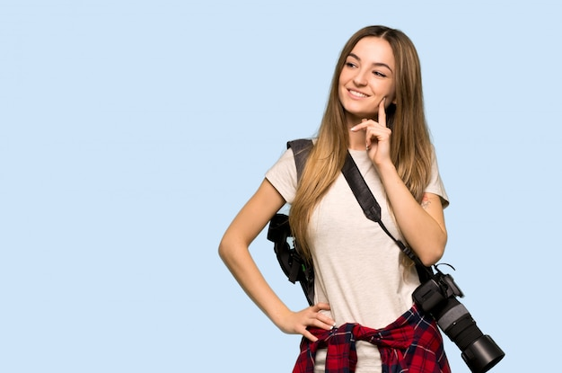 Junge fotograffrau, die eine idee beim oben schauen denkt