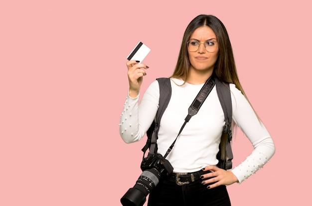 Junge fotograffrau, die eine kreditkarte auf lokalisiertem rosa hintergrund hält