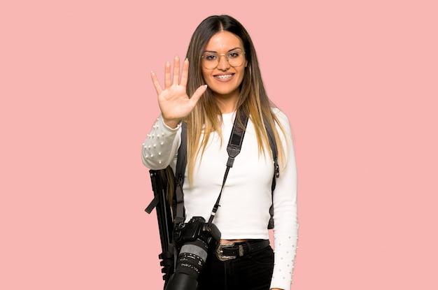 Junge fotograffrau, die fünf mit den fingern auf lokalisierter rosa wand zählt