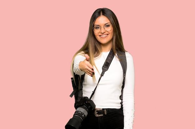 Junge fotograffrau, die hände für das schließen eines guten deals auf lokalisiertem rosa hintergrund rüttelt