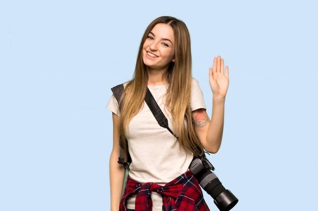 Junge fotograffrau, die mit der hand mit glücklichem ausdruck auf blauer wand begrüßt