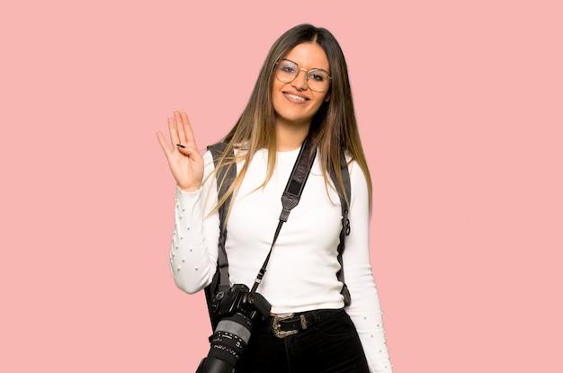 Junge fotograffrau, die mit der hand mit glücklichem ausdruck auf lokalisiertem rosa hintergrund begrüßt