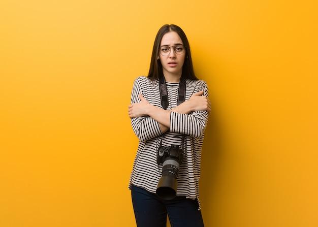 Junge fotograffrau, die wegen der niedrigen temperatur kalt geht