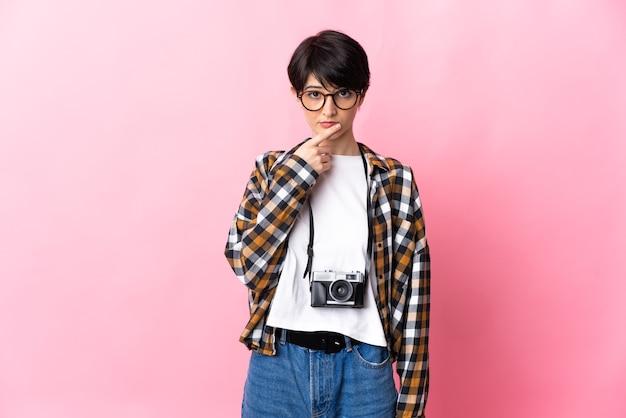 Junge fotograffrau lokalisiert auf rosa hintergrunddenken