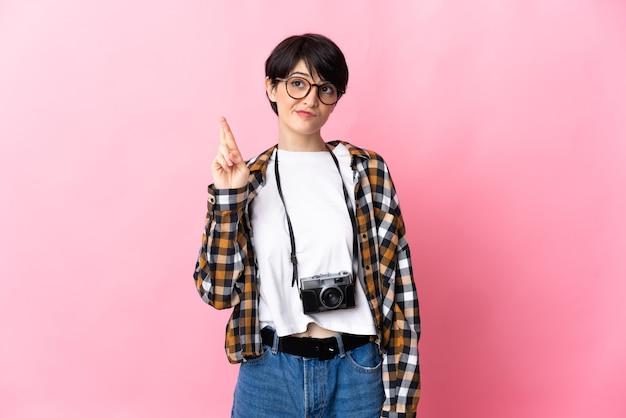 Junge fotograffrau lokalisiert auf rosa wand mit den fingern, die kreuzen und das beste wünschen
