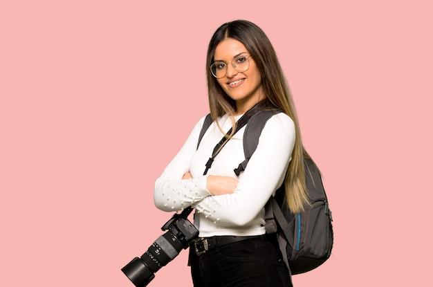 Junge fotograffrau mit den armen gekreuzt und auf lokalisierter rosa wand vorwärts schauend