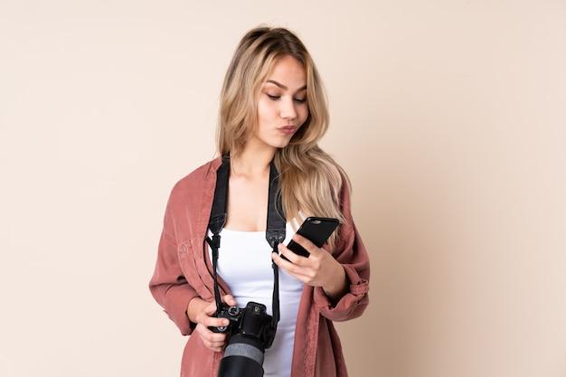 Junge fotograffrau über isolierte wand, die eine nachricht denkt und sendet