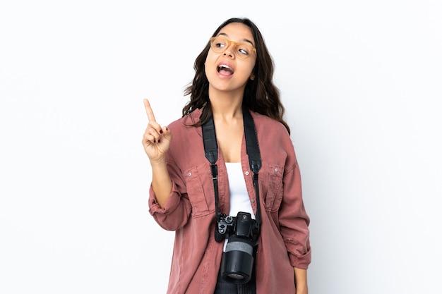 Junge fotograffrau über isoliertem weißem hintergrund, der beabsichtigt, die lösung beim anheben eines fingers zu realisieren
