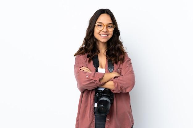 Junge fotograffrau über isoliertem weißem hintergrund, der die arme in der frontalposition verschränkt