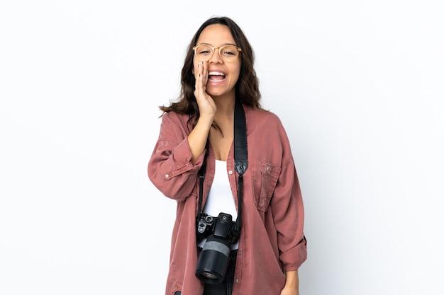 Junge fotograffrau über isoliertem weißem hintergrund, der mit dem mund weit offen schreit