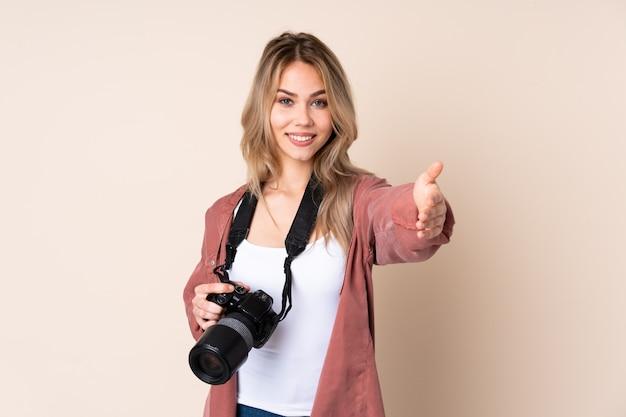Junge fotograffrau über isolierter wand, die präsentiert und einlädt, mit hand zu kommen