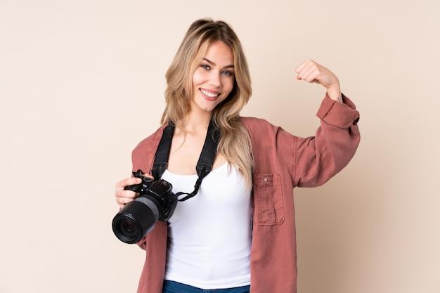 Junge fotograffrau über isolierter wand, die starke geste tut