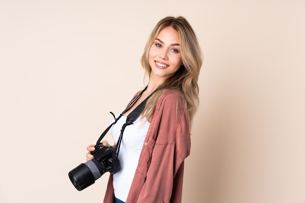 Junge fotograffrau über isolierter wand mit verschränkten armen und nach vorne schauend