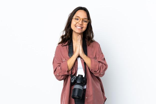 Junge fotograffrau über isolierter weißer wand hält handfläche zusammen. person fragt nach etwas