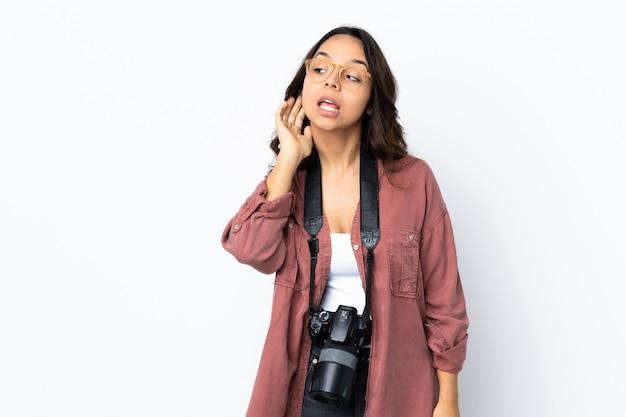 Junge fotograffrau über weißer wand, die etwas hört, indem man hand auf das ohr legt